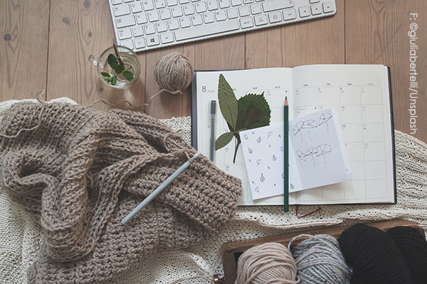 stricken mit wolle und ein notizbuch