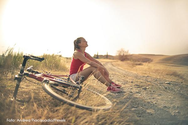 Frau sitzt am Wegrand, Fahrrad liegt daneben