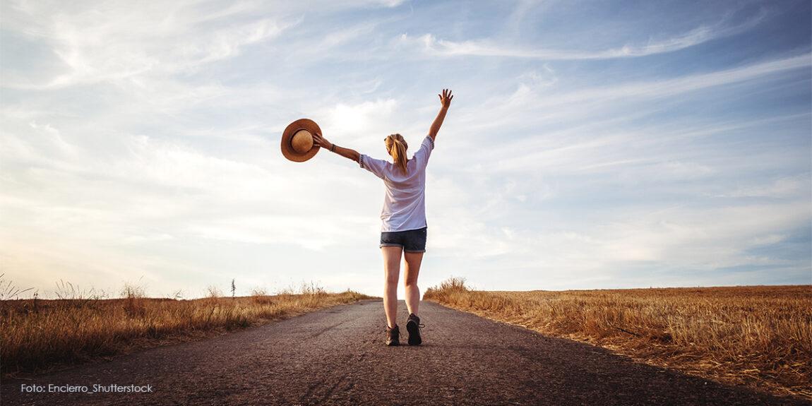 Frau mit Sonnenhut in der Hand geht auf der Straße